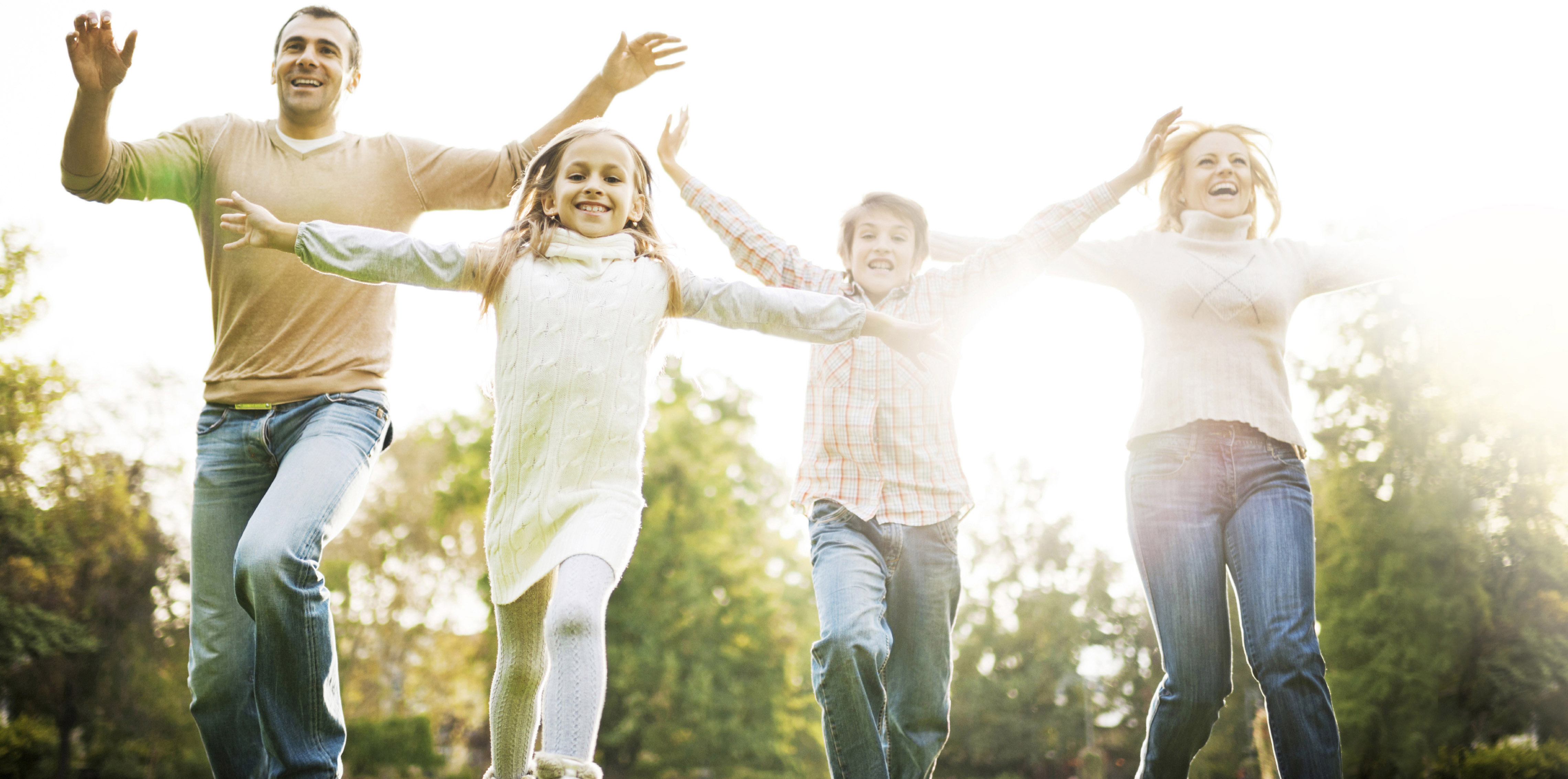 Low angle view of cheerful family having fun while running in the park.  [url=http://www.istockphoto.com/search/lightbox/9786778][img]http://dl.dropbox.com/u/40117171/family.jpg[/img][/url]